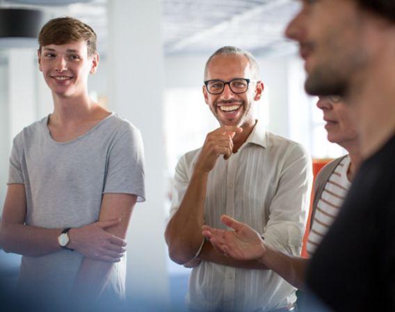 Bilde av fire smilende kollegaer i et møte