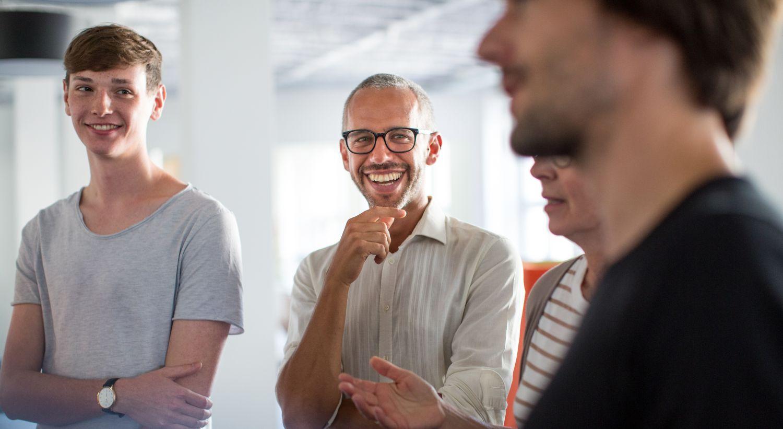 Bilde av fire kollegaer som smiler