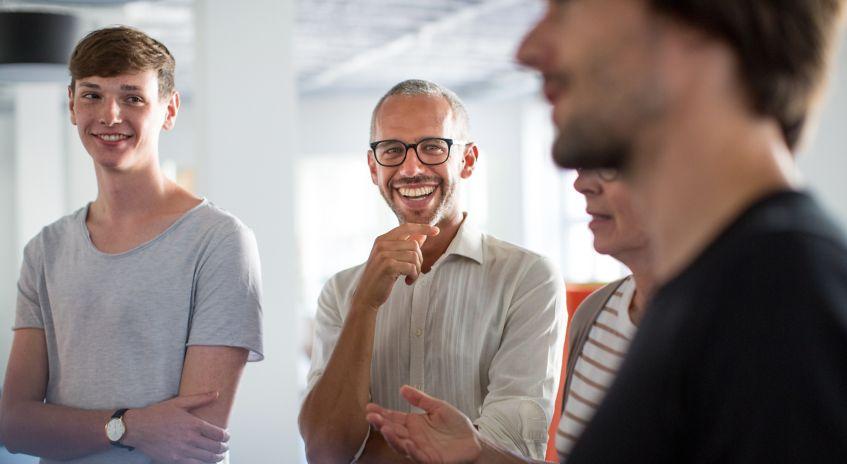Fire personer står og prater og smiler