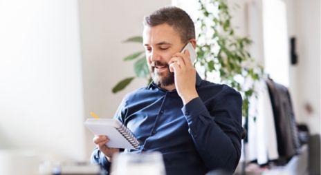 Mann snakker i telefonen og ser i en notatbok. Foto.