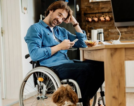 Bilde av mann som sitter i rullestol og smiler til hunden sin