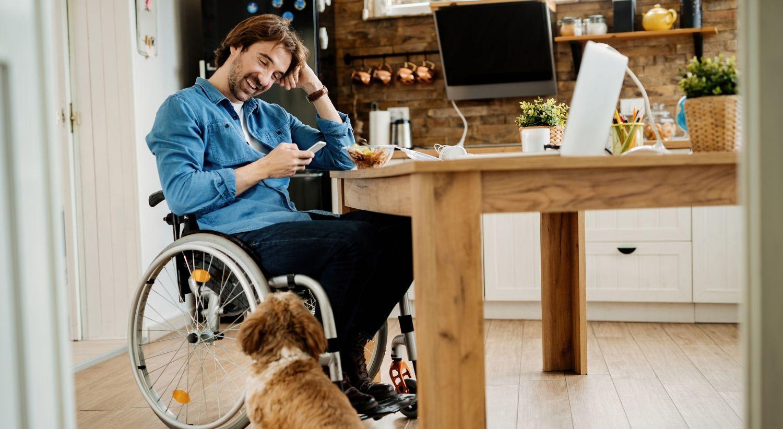 Bilde av mann i rullestol som ser på mobilen med en hund ved siden av seg.