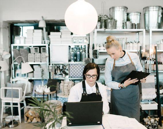 Bilde av to kvinnelige kollegaer som ser på ser på en datamaskin i en butikk