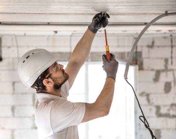 Bilde av en elektrikerinstallatør med et verktøy i hendene, som arbeider med kabel på byggeplassen