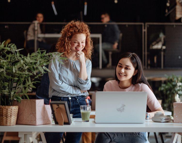 To kvinner ser på en datamaskin og tenker