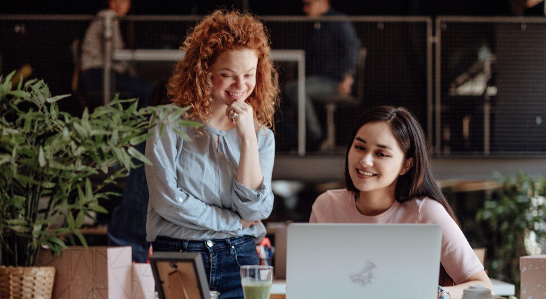 Bilde av to kvinnelige kolleger som ser på ser på en datamaskin i en butikk