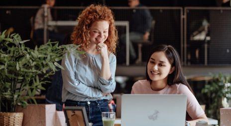 To kvinner smiler og ser på en datamaskin. Foto.
