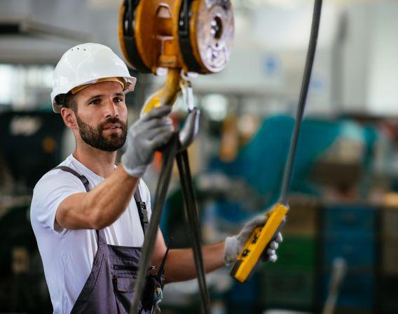 Bilde av en mann som jobber på fabrikk og bruker løftebjelke