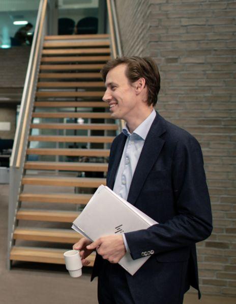 Smilende mann med PC under armen og kaffekopp i hånden