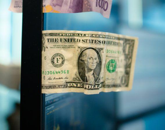 Hos DNB Markets kan du handle med både valuta og rentepapirer. Illustrasjonsfoto dollar og  rupi