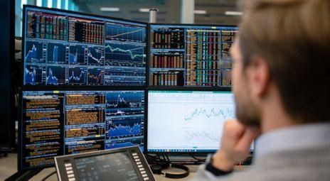 Mann foran skjerm med mange grafer