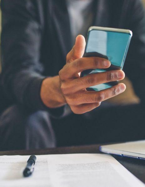 Mann bruker smarttelefon og laptop på hjemmekontor