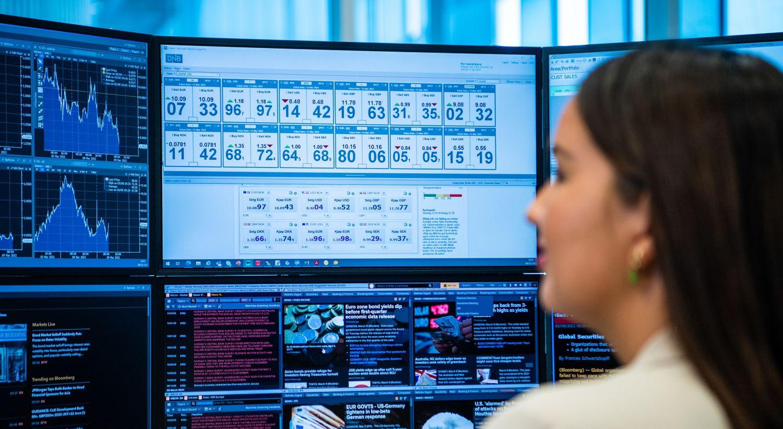 Ung kvinne sitter og følger med på valutakurser på en skjerm