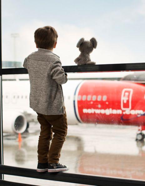 Liten gutt som ser på Norwegian-fly