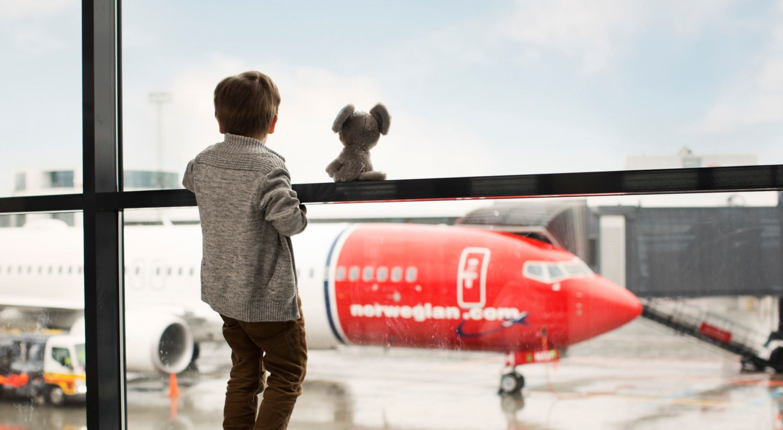 Gutt ser på Norwegian-fly og drømmer. Informasjon om emisjonen - illustrasjonsfoto.