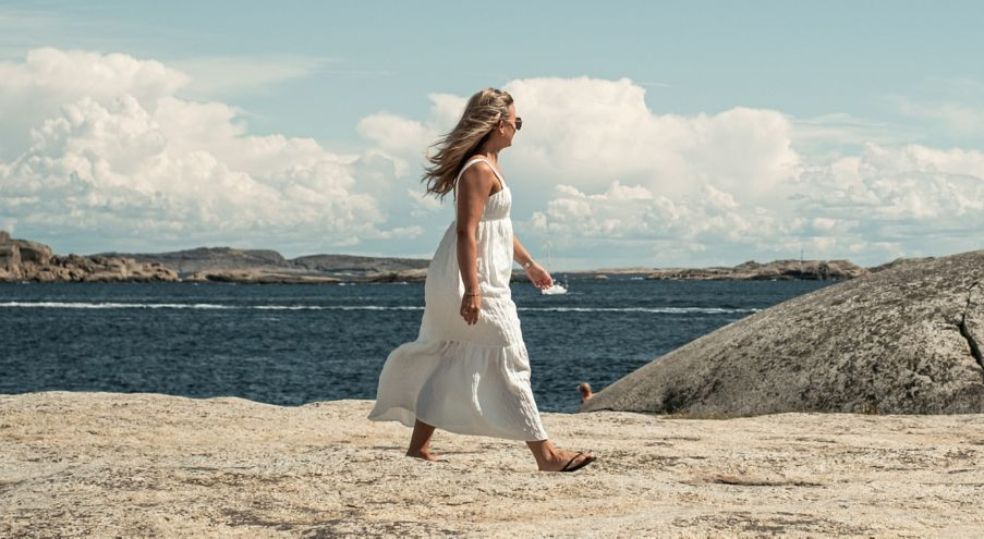 Kvinne spaserer på svaberg i sommerkjole