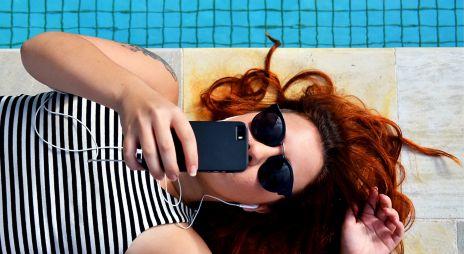 Dame som ligger ved et basseng og lytter på mobilen