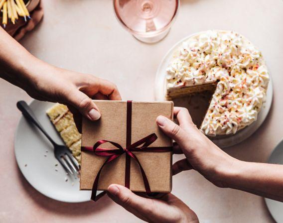 Bilde av gave med rødt bånd og kake på bord