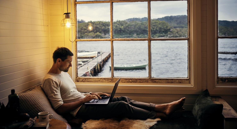 Mann med PC på sjøhytte
