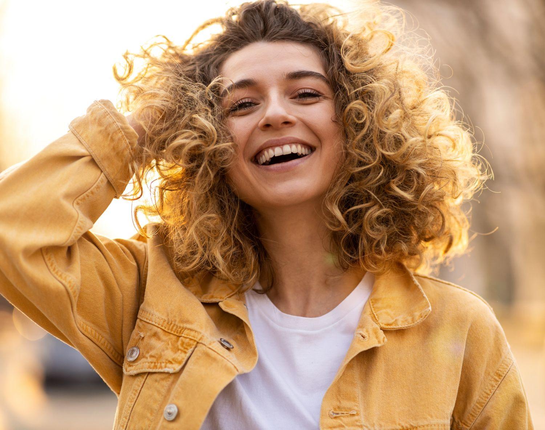 Ung smilende dame med krøllete hår