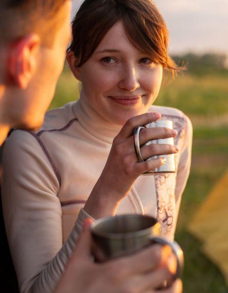 Par som drikker kaffe utenfor telt