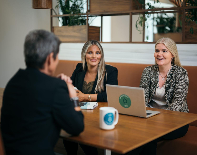 Oppstartslosene sitter ved et bord og diskuterer. Foto