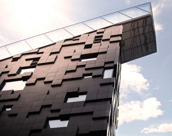 Bilde av en moderne, sort bygning med blå himmel rundt